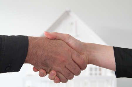 Two people (male and female) are shaking hands against a white house. Mortgage, housing market, home loans and property, management concept. No people. Copy space Stock fotó