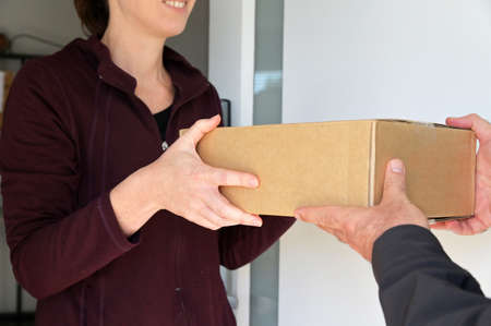 Woman receiving a package from a currier at home front door.