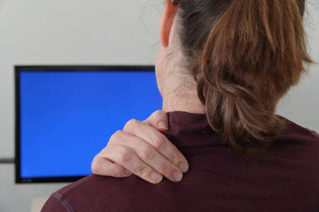 Close up of a woman working on a computer and suffering from back, shoulder and neck pain.