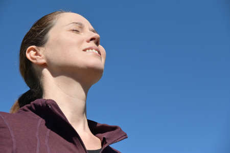 Happy adult woman (female age 30-40) with closed eye standing outdoors breathing clean fresh air isolated on clear blue sky.