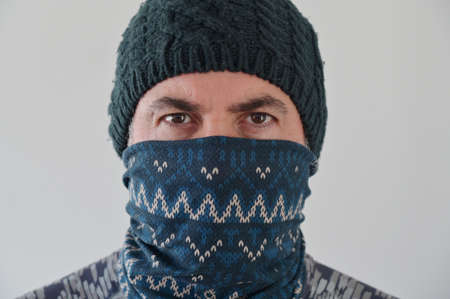 Middle Eastern Militant Man disguising his identity by wearing a beanie and balaclava face cover looking at camera.