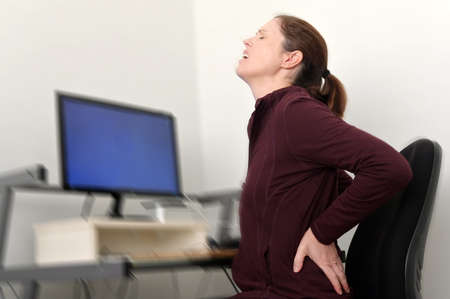 Woman working on a computer at a home office is suffering from lower back pain.