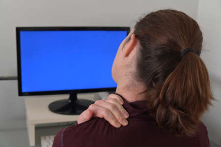 Woman working on a computer is suffering from back, shoulder and neck pain. Stock fotó