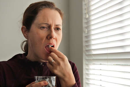 Sick woman (female age 30-40) taking a medical pill with glass of water.