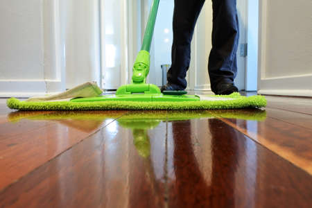 Person mopping a wooden floor at home corridor. Stock fotó