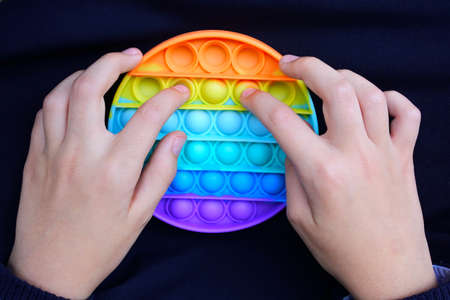 POV (point of view) of a young child playing with push pop it bubble fidget sensory toy in rainbow colors.