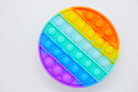 Flat lay of a round Push pop it bubble fidget sensory toy in rainbow colors. Stock fotó