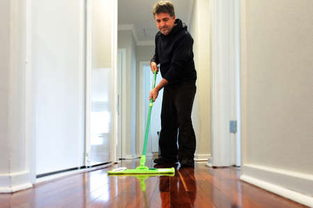 Mature adult man (age 40-50) mopping a wooden floor at home corridor.