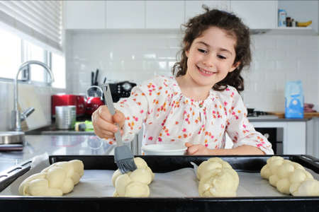 Happy young Jewish girl (female age 7) baking sweet Challah bread for Sabbath Jewish Holiday in home kitchen. Stock fotó