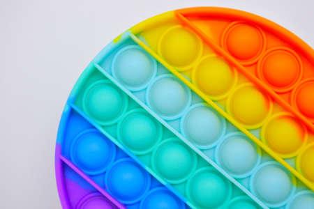 Close up of round Push pop it bubble fidget sensory toy in rainbow colors.