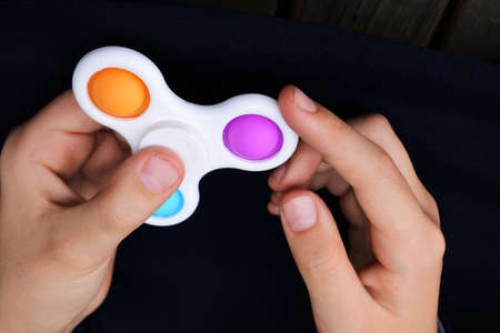 POV (point of view) of child hands playing with pop it fidget spinner toy.