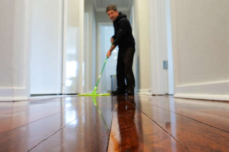 Adult man mopping a wooden floor at home corridor. Focus on foreground
