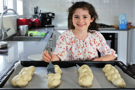 Cute young Jewish girl (female age 7) looking at camera, baking sweet Challah bread for Sabbath Jewish Holiday in home kitchen. Stock fotó