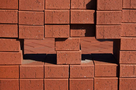 Piles of new red bricks abstract background and texture.