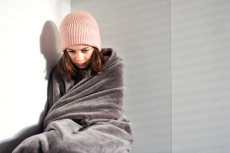 Sad young girl (female age 11-12) wearing a beanie sitting in the corner covered with warm blanket. Real people. Copy space Stock fotó
