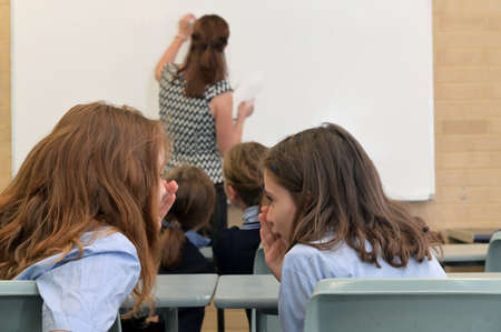 Two school girls whispering secrets in classroom behind teachers back.