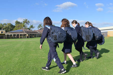 Group of Australian school girls wearing school uniform walking together to school in the morning time. Stock fotó