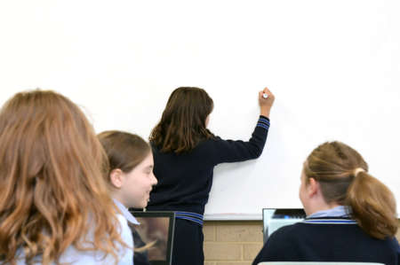 Rear view of primary schoolgirl student writing on a clear whiteboard in classroom with students.