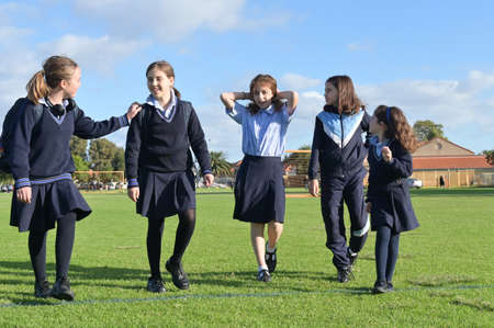 Group of Australian school girls wearing school uniform walking together back home from primary school in the afternoon time.