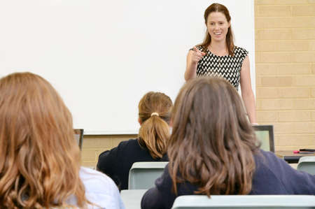 Front view of a happy school teacher (female age 30-40) teaching students in a classroom. Stock fotó