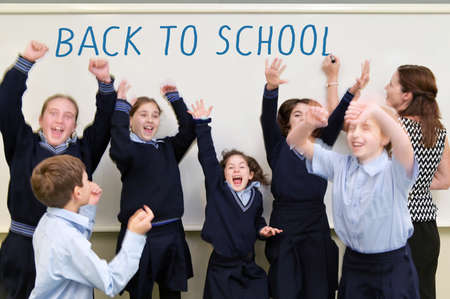 Group of happy schoolchildren jumping in the air while teacher (female age 30-40) writing: Back To School on a  whiteboard in classroom. Stock fotó