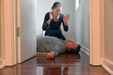 Adult woman (female age 30-40) with expression of panic looking at a mature adult man (male age 40-50) lying on bedroom floor unconscious Stock Photo