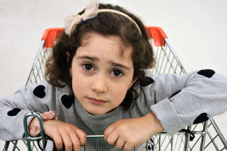 POV (point of view) of a parent looking down at upset young daughter girl sitting inside a shopping trolly.