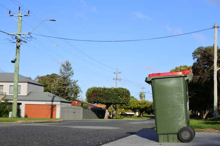 Waste bin ready for pick up by a waste collection truck outside a home on a  suburbian street