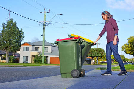 An adult Australian woman (female age 30-40) puts recycling bins outside her home on waste collection day