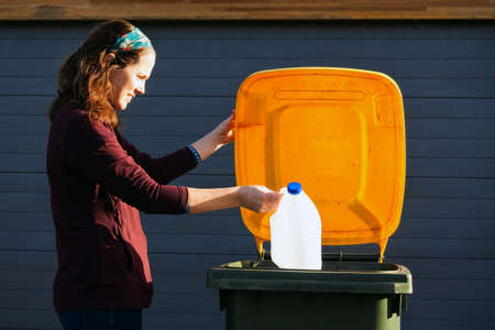 An adult Australian woman (female age 30-40) puts a plastic milk bottle into a yellow recycling bin outside her home on waste collection day
