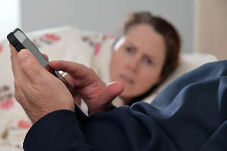 Upset adult woman (female age 30-40) looking at man hands using mobile phone lying in bed. Banque d'images