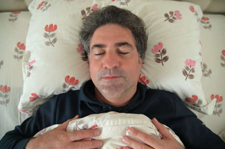 Mature adult man (male age 40-50) sleeping in bed in the bedroom.
