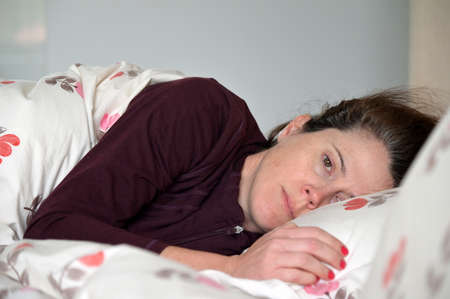 Adult woman (female age 30-40) lying down in bed suffering from depression looking at camera. Banque d'images