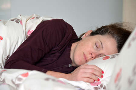 Adult woman (female age 30-40) sleeping in bed .