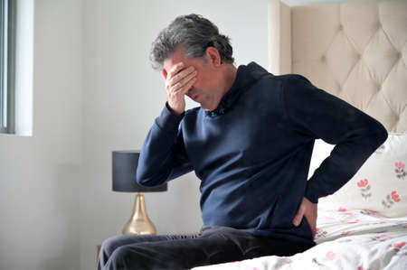 Mature adult man (male age 40-50) sitting on a bed in the bedroom suffers from a severe back pain covers his face.