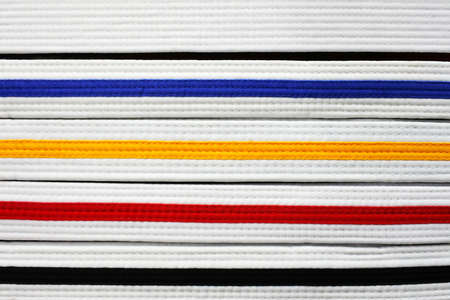 Coloured East Asian martial arts belt ranks: Black, red , yellow, blue and white abstract background and texture.