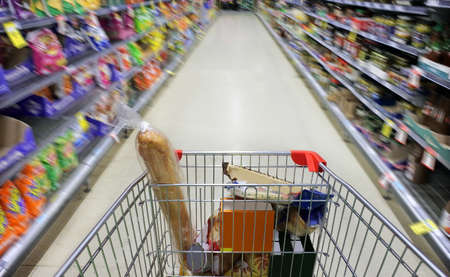 POV (point of view) of person pushing in motion blur of shopping cart rushing in supermarket ally full with food merchandise.