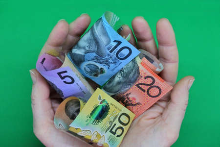 POV (point of view) of adult businessman person holding Australian dollar currency bank notes with his two hands isolated on a green background. No people. Copy space Banque d'images