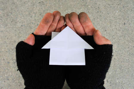 POV (point of view) of a poor person holding a house made out from Origami art of paper folding with his two hands in city street. Mortgage bank loans interest rate and real estate property concept.