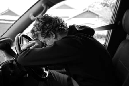 A sad and depressed mature adult man (male age 40-50) sitting in a car leaning on vehicle steering wheel outside his home. Banque d'images