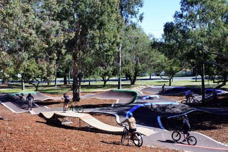 PERTH, WA - AUG 14 2021: Group of BMX cyclists biking in outdoor cycling public park.