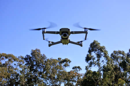 Front view of a Drone flying fast above forest treetops. Banque d'images