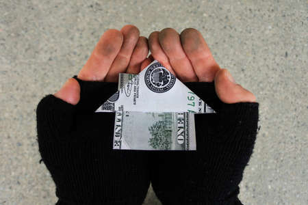POV (point of view) of a Homeless person holding a house made out from Federal reserve US dollar with his two hands in city street. Mortgage bank loans interest rate and real estate property concept.