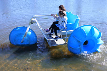 Aerial view of two young girls sisters (age 11-12 and 7-8) riding on a big wheel aqua bike water tricycle  over a lake waters.