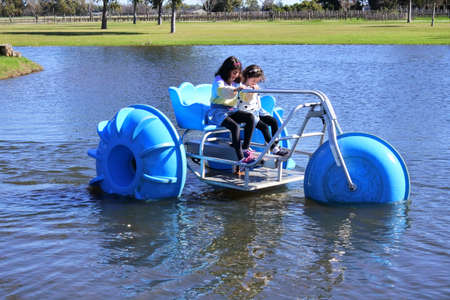 Two young girls sisters (age 11-12 and 7-8) riding on a big wheel aqua bike water tricycle  over a lake waters.