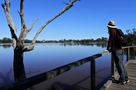A local adult Australian woman (female age 30-40) hiking outdoors during the weekend looking at the Swan river in Perth Western Australia.