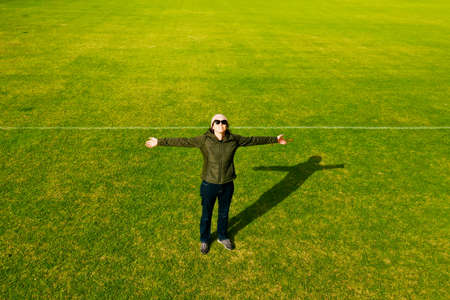 Aerial view of happy active adult woman looking up with open arms on a green grass. Banque d'images