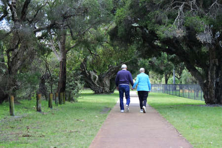 Active senior couple holding hands walking together on a footpath in a public park.