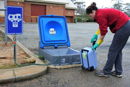 Australian woman emptying a caravan tank toilet cassette in a dump point during a road trip in Western Australia.It's a facility intended to receive the discharge of RV wastewater.