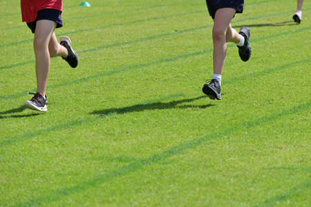 Group of unrecognizable runners running fast on grass running track outdoors.
